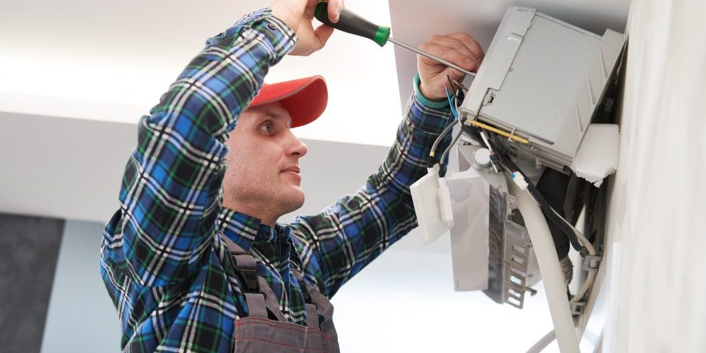Air Conditioner Service. Worker At Climatization System Installation Indoors